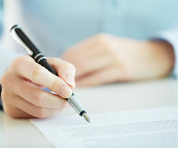 person holding pen writing on a form