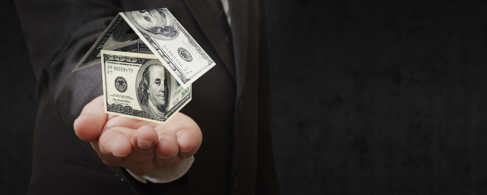 Man holding a small house in his hands made up of $100 dollar bills
